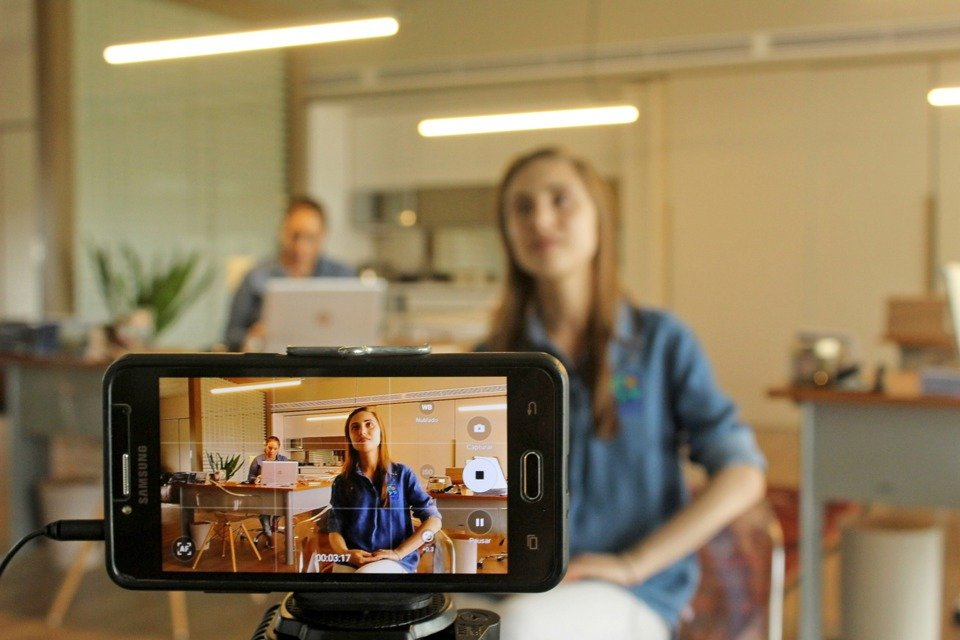 A woman sits in an office as we view her through a smartphone camera